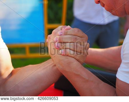 Men Are Fighting Arm Wrestling By Clenching Their Hands Tightly. Closeup Photo