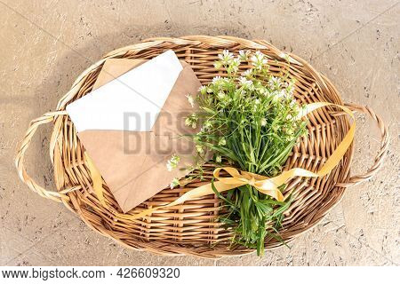 Wicker Tray With Bouquet Of Windflowers Tied With Golden Ribbon And Card In Envelope On Beige Table