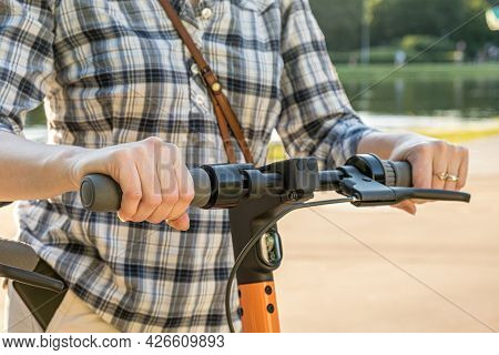 Woman In A Checkered Shirt Holds The Wheel Of An Electric Scooter In A City Park. Close-up Of Hands