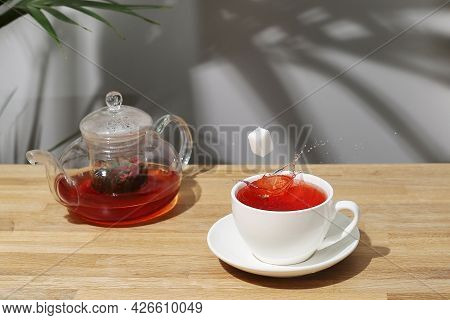 Ref Fruit Tea On Wooden Table. Sugar Cube Falling In Cup. Splash Of Tea. Tea Pot With Fruit Tea