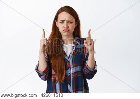 Skeptical Redhead Woman Grimacing, Cringe And Frown Pointing Up At Bad Thing, Disappointed, Express