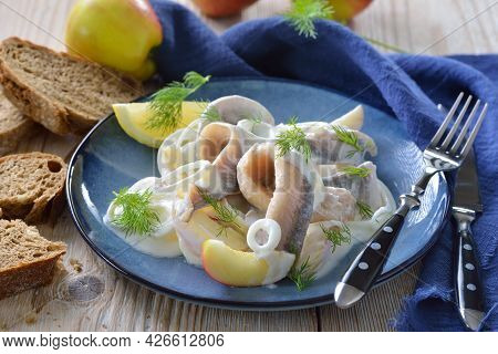 Salty Herring Fillets With Apple Slices, Onion Rings And Yoghurt Cream Sauce