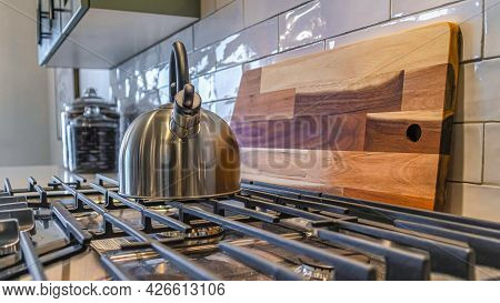 Pano Cooktop With Kettle Over Burner And Cast Iron Grate Inside A Residential Kitchen