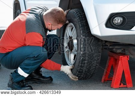 A Car Mechanic In A Medical Mask Changes A Wheel On A Car On The Street On A Sunny Day. Help On The