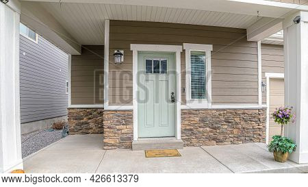 Pano Front Door And Sidelight Against Brick Wall And Wood Siding Of Home With Porch