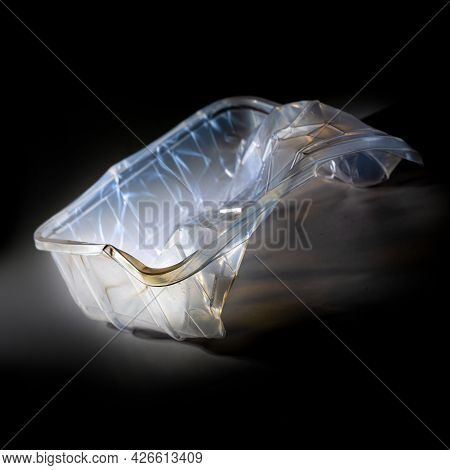 Empty Plastic Packaging For Food Shown Like An Art Sculpture Against A Black Background, Waste Of Th