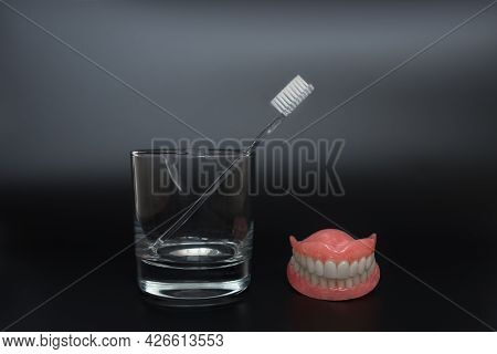 Full Removable Plastic Denture Of The Jaws. Two Acrylic Dentures. Dental Care With An Toothbrush. Te