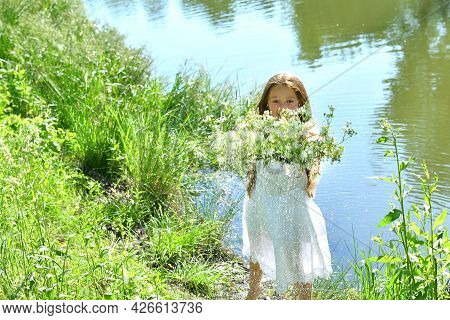 Beautiful Girl In White Dress Putting Flowers Wreath On River Water Surface.feast Of Ivan Kupala.mid