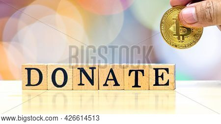 Donate Concept Idea, Close-up Hands Of Man Who Holding Gold Coin For Give To Donate Wooden Letters O