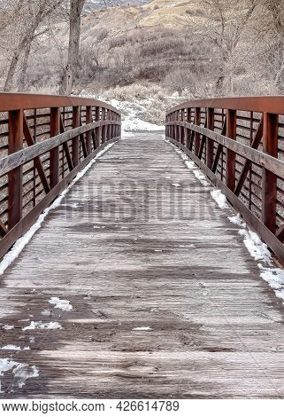 Vertical Wooden Bridge Over Creek In The Mountain With Leafless Trees On Snowy Winter Day