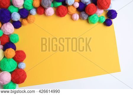 A Background Of Many Multicolored, Scattered Woolen Balls Of Knitting Yarn With An Empty Space For T