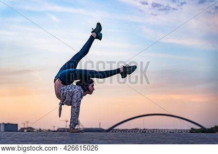 Silhouette Of Flexible Woman Doing Handstand On The Dramatic Sunset And Cityscape. Concept Of Indivi