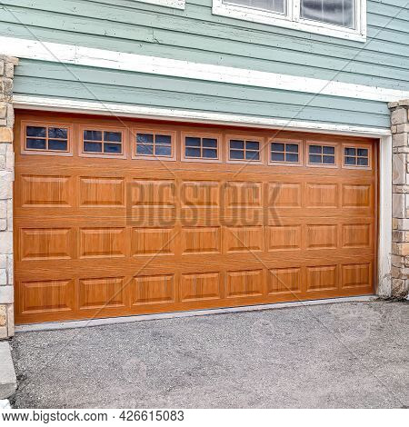 Square Wide Brown Door With Glass Panes Of A Two Car Garage Of Home With Green Wall
