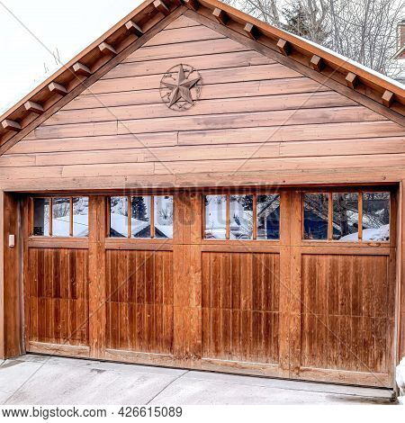 Square Garage Exterior With Snowy Gable Roof Over Glass Paned Door And Wooden Wall.