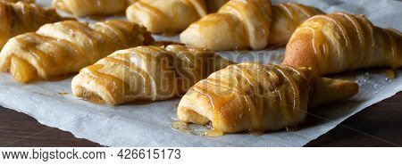Narrow View Of A Parchment Lined Baking Sheet Topped With Rows Of Freshly Baked Crescent Rolls Toppe