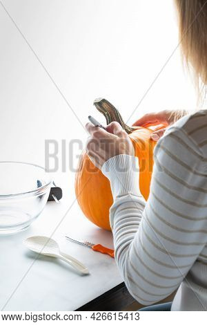 Woman Drawing On A Pumpkin, Preparing It For Carving For Halloween.