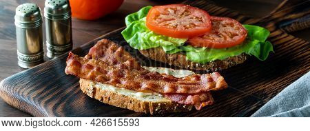 Narrow View Of A Bacon And Tomato Sandwich Opened Up To See The Ingredients, On A Wooden Board.