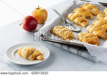 Apple Filled Crescent Roll On A Small Plate With A Baking Sheet Of More In Behind, Against A Bright