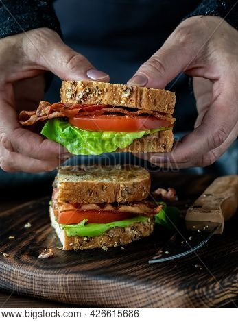 Hands Holding One Half Of A Homemade Bacon And Tomato Sandwich, Ready To Take A Bite.