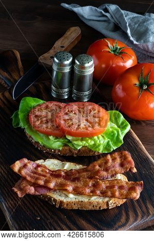 Vertical View Of A Homemade Open Bacon And Tomato Sandwich With Tomatoes, Salt And Pepper Shakers An