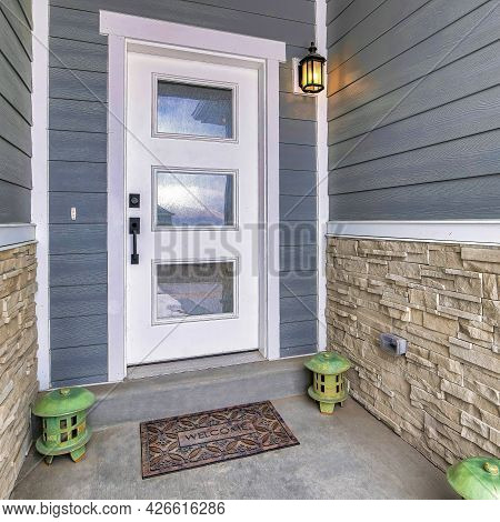 Square White Front Door With Glass Panes At Home Entrance With Lanterns On The Doorstep