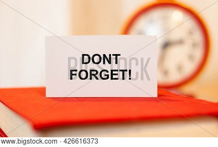 Dont Forget - A Reminder On Paper Against The Background Of A Clock.