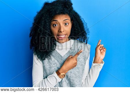 African american woman with afro hair wearing casual winter sweater pointing aside worried and nervous with both hands, concerned and surprised expression