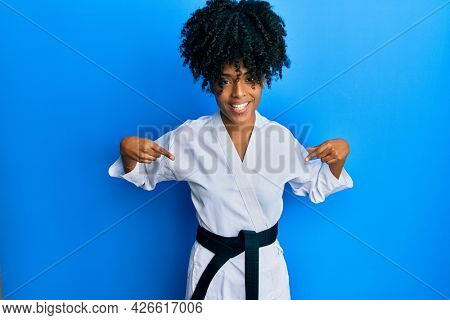 African american woman with afro hair wearing karate kimono and black belt looking confident with smile on face, pointing oneself with fingers proud and happy.