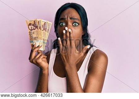 Young african american woman holding hungarian forint banknotes covering mouth with hand, shocked and afraid for mistake. surprised expression
