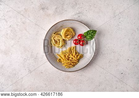 Uncooked Raw Girandole, Tagliatelle, Cherry Tomatoes And Basil On White Plate On Grey Textured Backg