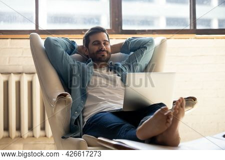 Serene Man Accomplish Work On Laptop Relaxing On Leather Armchair