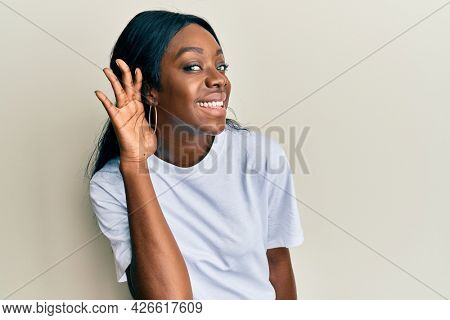 Young african american woman wearing casual white t shirt smiling with hand over ear listening and hearing to rumor or gossip. deafness concept.