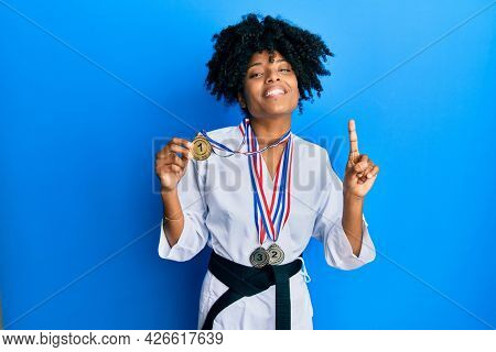 African american woman with afro hair wearing karate kimono and black belt holding medals smiling with an idea or question pointing finger with happy face, number one