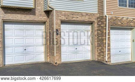Pano Townhouses With White Garage Doors Against Brick Exterior Wall And Wood Siding