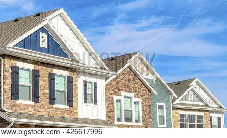 Pano Exterior View Of Homes With Gable Roofs Stone Brick And Wooden Siding Walls