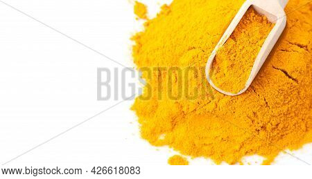 Pile Of Turmeric Or Curcuma Powder With Wooden Scoop Isolated On White Background Wih Copy Space. To