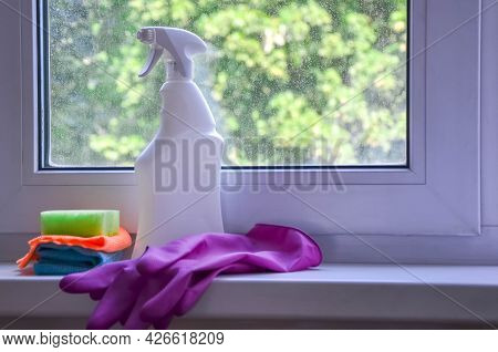 Spray Bottle With Window Cleaner, Rag And Cleaning Sponge Lie On Windowsill Against Backdrop Of Dirt