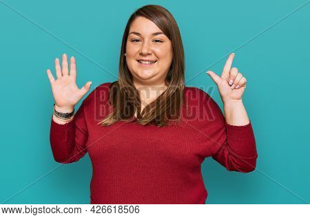 Beautiful brunette plus size woman wearing casual clothes showing and pointing up with fingers number seven while smiling confident and happy.
