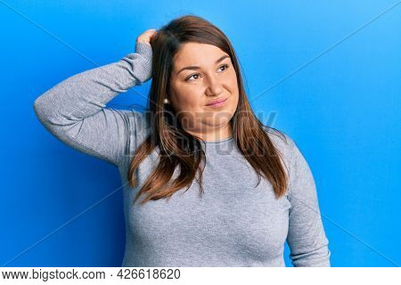 Beautiful brunette plus size woman wearing casual clothes confuse and wonder about question. uncertain with doubt, thinking with hand on head. pensive concept.