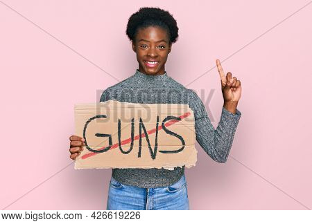 Young african american girl holding no guns warning banner surprised with an idea or question pointing finger with happy face, number one