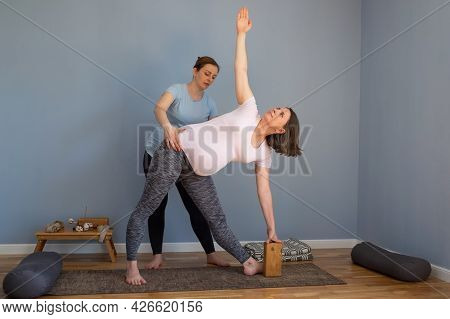 Pregnant Yoga Model Working Out Indoo Doing Extended Triangle Pose