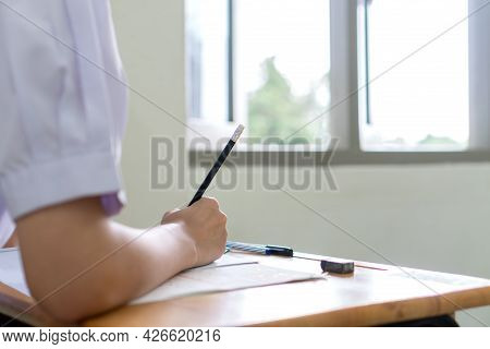 Writing On Exam Test In Classroom. Asian Young Student Holding Pencil Taking Exams On Answer Sheet E
