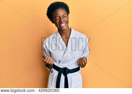 Young african american girl wearing karate kimono and black belt very happy and excited doing winner gesture with arms raised, smiling and screaming for success. celebration concept.