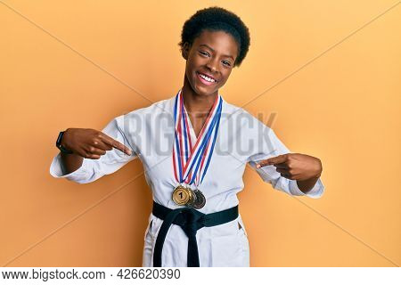 Young african american girl wearing karate kimono and black belt looking confident with smile on face, pointing oneself with fingers proud and happy.