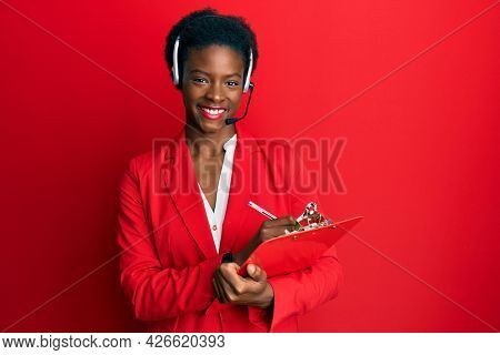 Young african american girl wearing call center agent headset writing on clipboard smiling with a happy and cool smile on face. showing teeth.