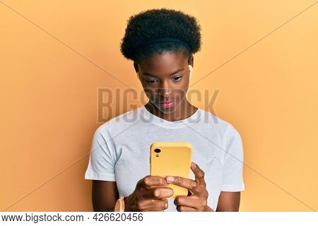 Young african american girl using smartphone and earphones relaxed with serious expression on face. simple and natural looking at the camera.
