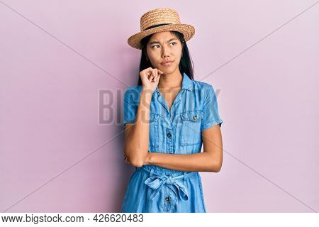 Young chinese woman wearing summer hat thinking concentrated about doubt with finger on chin and looking up wondering