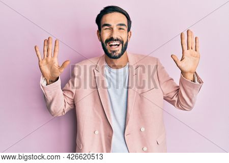 Young hispanic man wearing business jacket showing and pointing up with fingers number ten while smiling confident and happy.
