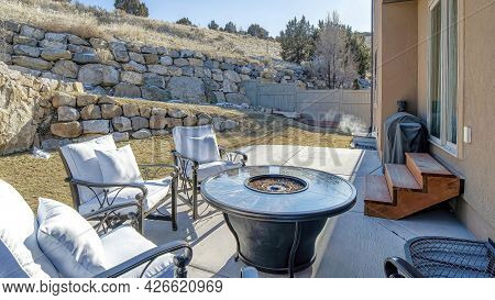 Pano Fire Pit And Paved Patio At Sunny Backyard Of House With Stone Retaining Wall