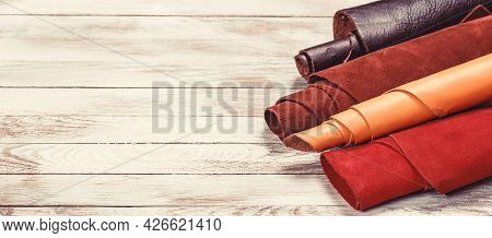 Rolls Of Natural Color Leather. Materials For Leather Craft On Wooden Background. Raw Materials For